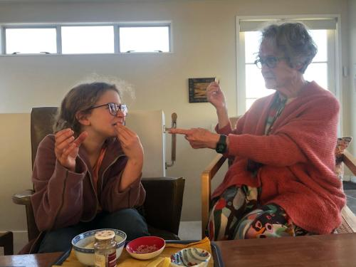 young poet and old poet talking and eating a snack