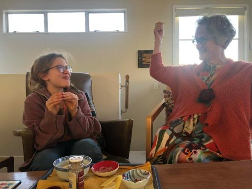 Young poet and old poet both enjoying tiny sandwiches made of green apples, chili and cheese