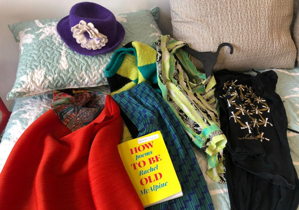 Clothes on a bed: red dress, purple hat, green and blue jumper, shirt and trousers, black tights and starry black tee shirt. Book, How To Be Old by Rachel McAlpine