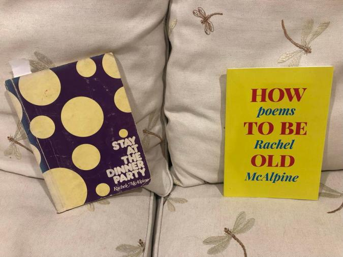 Two poetry books by Rachel McAlpine. Stay at the dinner party (old and worn, purple with yellow dots) and How To be Old (new, yellow and pink and blue-green).