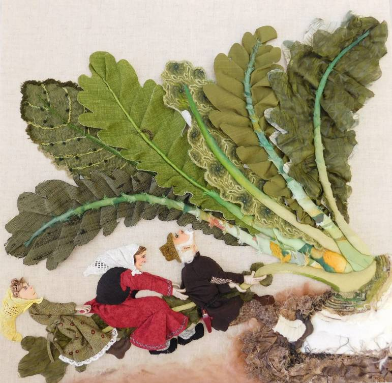 Photo of an embroidered illustration of three Russian characters pulling an enormous turnip out by the roots.