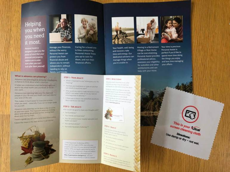 Two pamphlets and a document. A, Helping you when you need it most, is easy to read. B, What is advance care planning? is pale and hard to read. C, a screen cleaning cloth, is very easy to read.