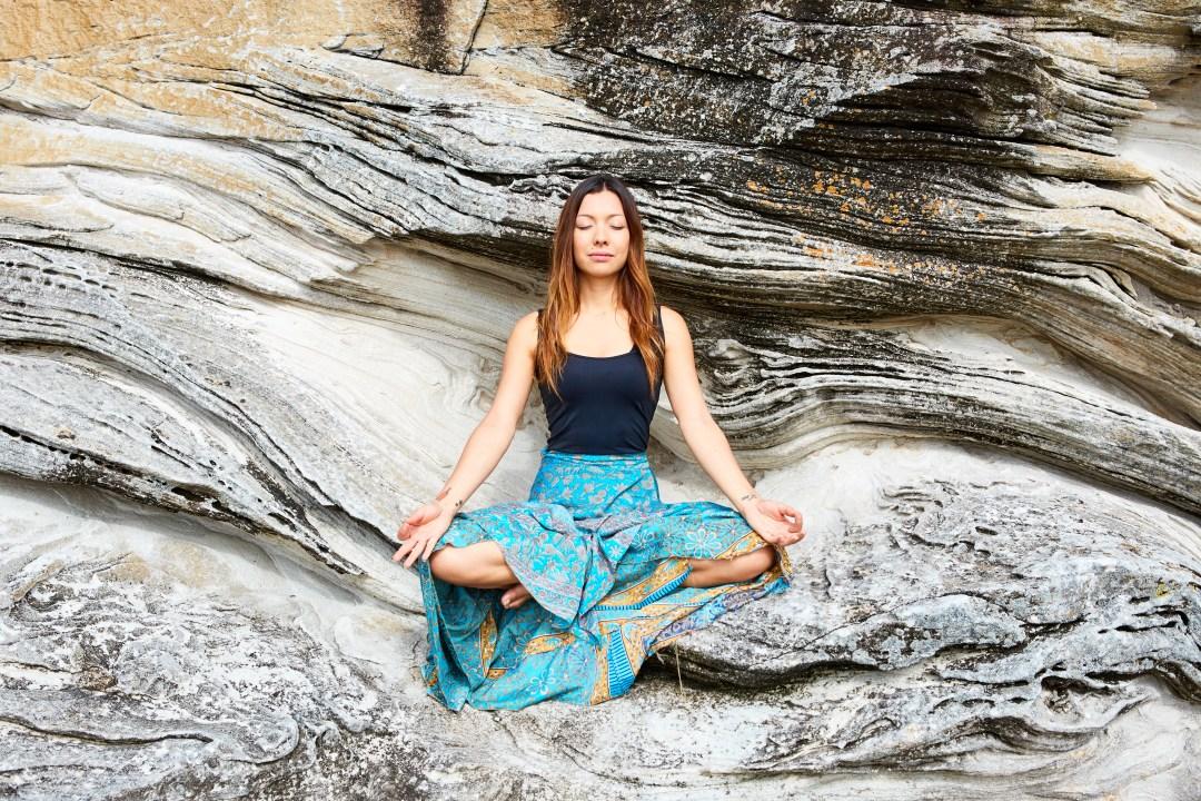 A girl sitting on rocks in a serene meditative state