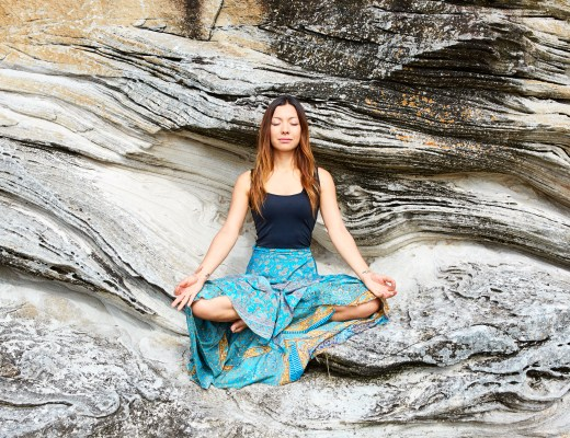 A girl sitting on rocks in a serene meditative state