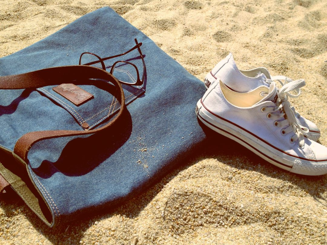 Ladies loafers and bag on the beach