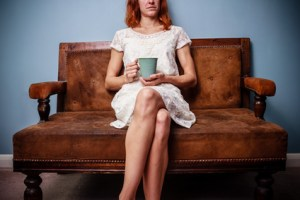 Young woman in summer dress sitting on old sofa drinking tea