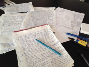 My desk covered in today's story notes and handwritten outline.