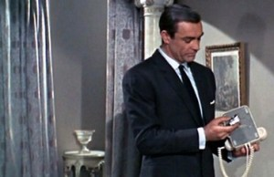 """James Bond checking the telephone for a bug. Of course, he finds one. Image from """"From Russia with Love."""""""