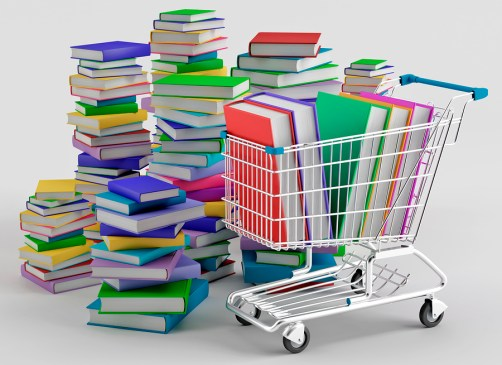 Stacks of colorful books next to a shopping cart