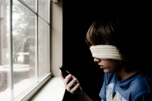 A blindfolded child tries and fails to look at a smart phone