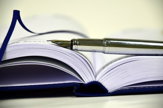 an image of an open book with a fountain pen balanced on top