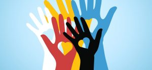 An image of 5 hands, each a different color. From top left: white, yellow, blue. From bottom left: red and black. Each contains a heart cut out.