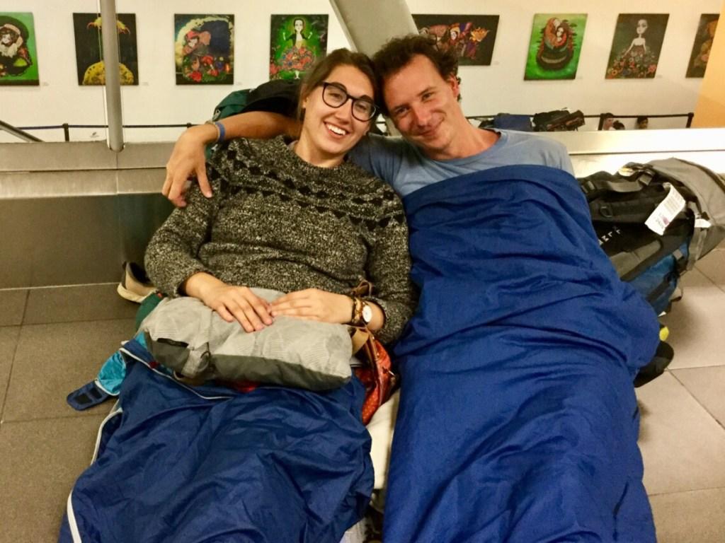 Two people in sleeping bags sleeping on the airport floor