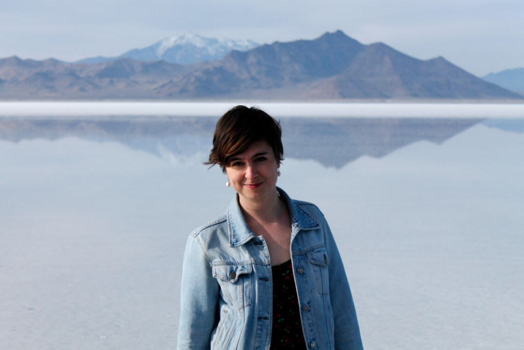 short haired woman standing in front of a lake