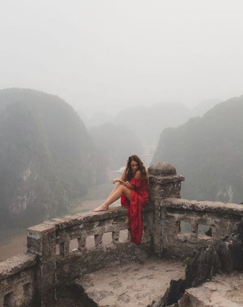 woman in a red dress sitting on a balustrade overlloking a river below