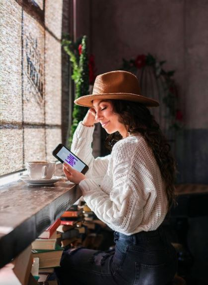 woman wearing a hat looking at her kindle with a cup of coffee on the table