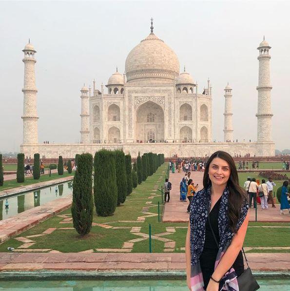 woman posing in front of the taj mahal