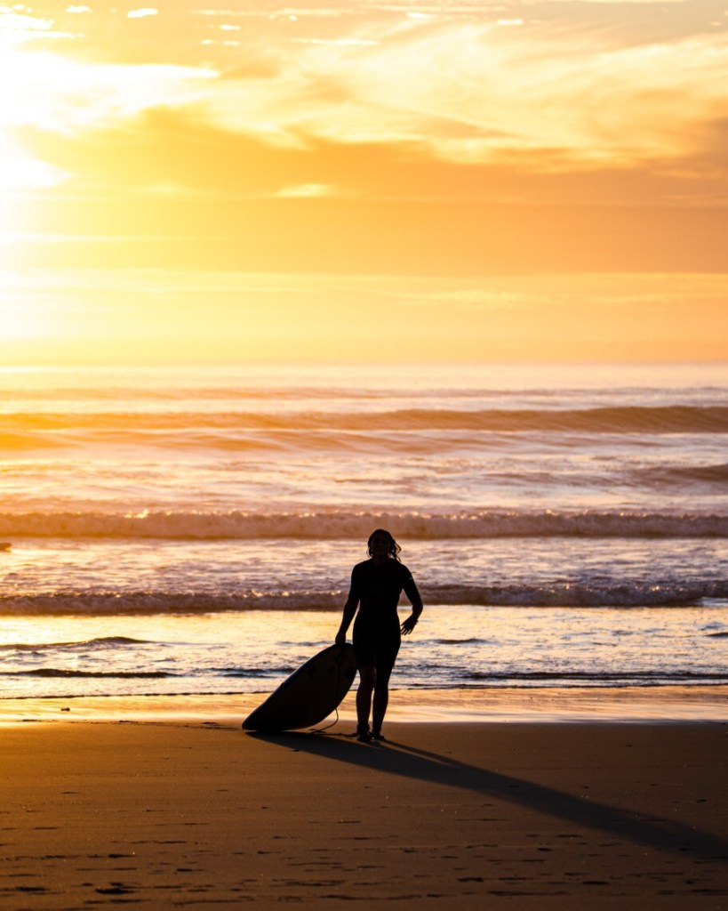 silhouet of a person with a surfboard walking on the beach at sunset