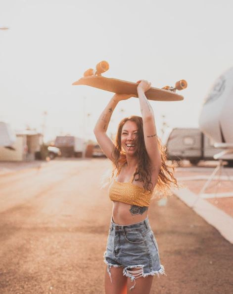 woman laughing while proudly holding up a skateboard