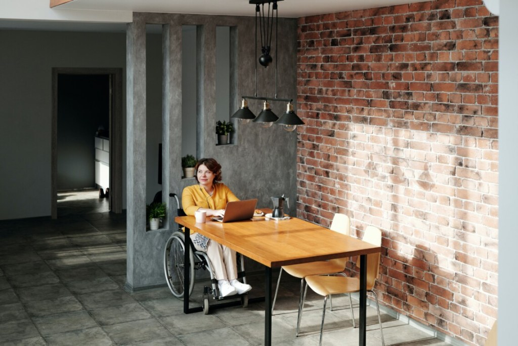 girl in a wheelchair at the table with a laptop on it