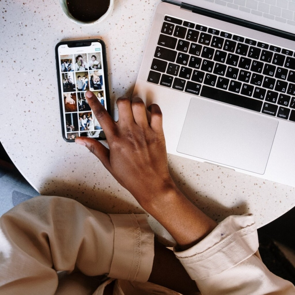 A Black woman sits at her laptop. You cannot see her face, but you see her hand on her phone