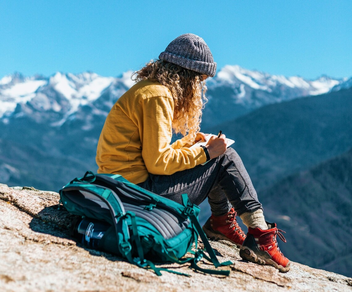 Curly-haired woman in hiking gear sites on ground writing in a notebook. Next to her is a backpack, and behind her are snowy mountain tops.