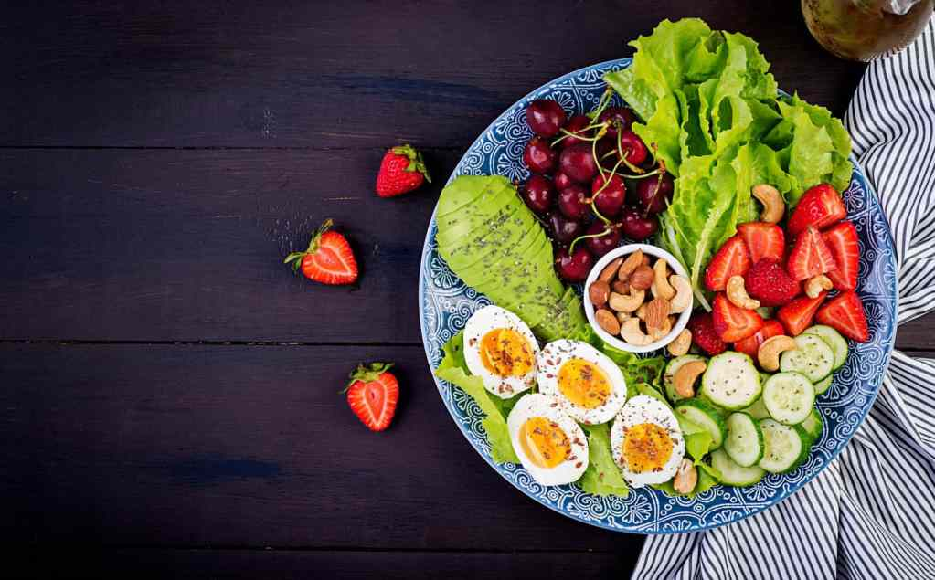 plate with paleo diet food boiled eggs avocado cucumber nuts cherry strawberries paleo breakfast top view scaled