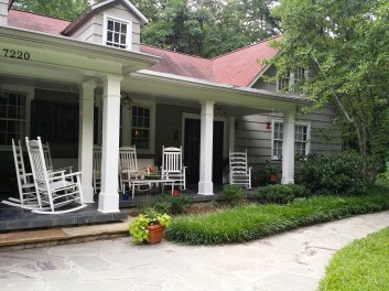 The porch of the retreat house with rocking chairs but no people