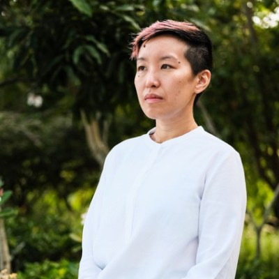 An image of JY Yang standing outside wearing a white shirt