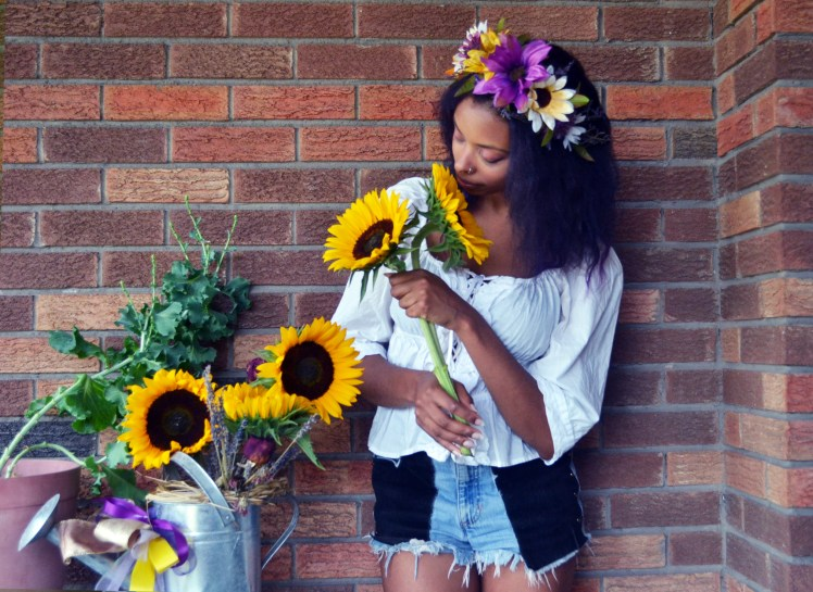Woman with flower crown and sunflowers.