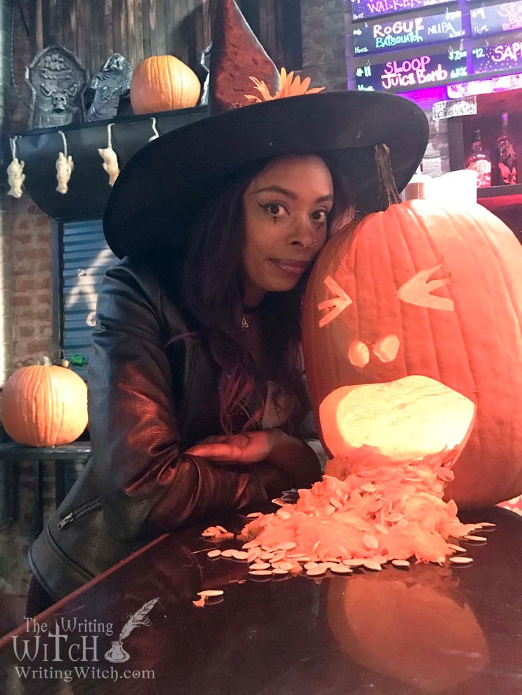 woman in a witch costume with a jack o lantern