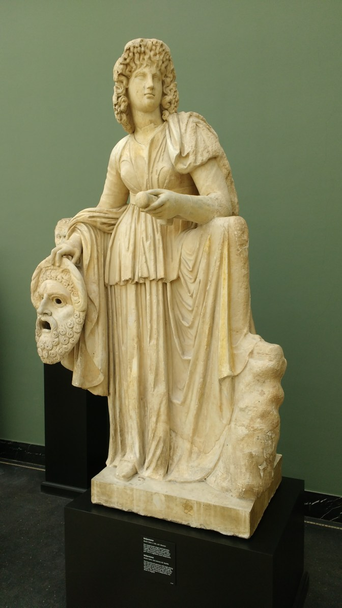 Actor who plays Dionysus holding his mask