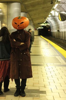 boston north station man with pumpkin head waiting for the train