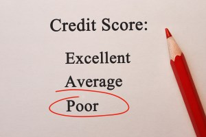 """Image of paper and red pencil with the words """"Credit Score"""" at the top and """"Poor"""" circled in red below it."""
