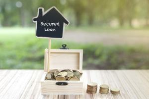 "Image of a wooden box filled with coins and a house shaped sign that reads ""Secured Loan""."