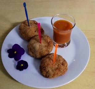 Plato con tres croquetas de berenjena acompañadas de salsa de tomate