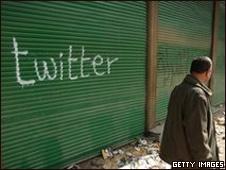 Hombre en Egipto frente a grafiti sobre Twitter