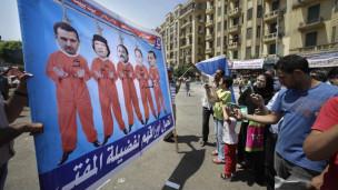 Manifestante egípcio exibe cartaz retratando o líder egípcio deposto, Hosni Mubarak, seu filho, Gamal, o líder deposto da Tunísia, Ali Abudalah Saleh, o líder deposto da Líbia, Muamar Khadafi e o presidente da Síria, Bashar al Assad, na Praça Tahrir (AP)