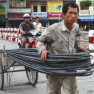 Một công nhân chở vật liệu tới công trường ở Hà Nội hôm 27/6