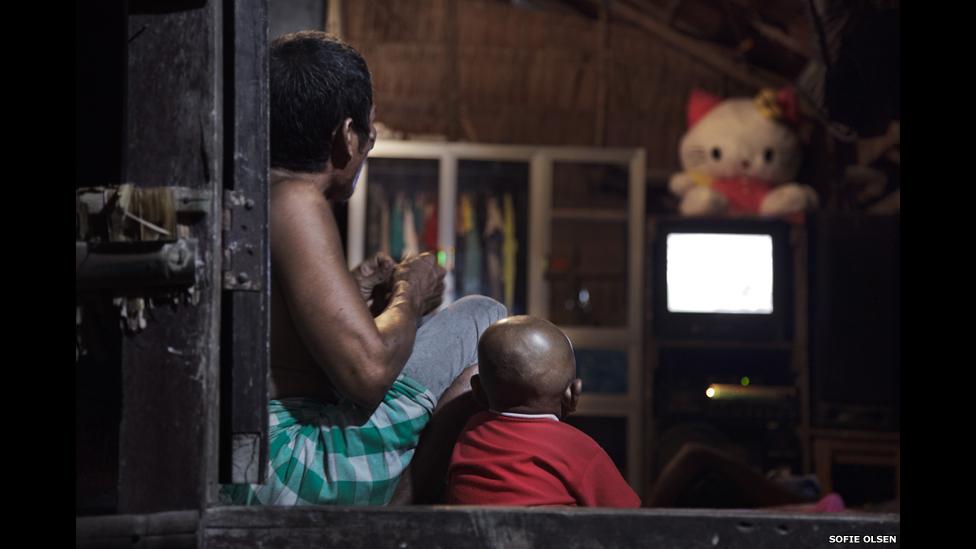 Un padre mira televisión junto a su hijo