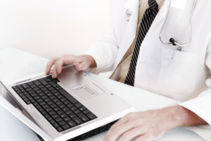 physician working at laptop