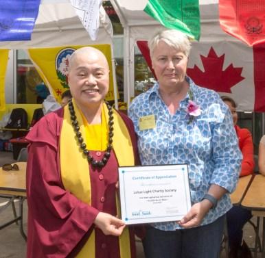 圖為溫哥華食物銀行代表頒發感謝狀給溫哥華華光功德會,由總裁蓮慈金剛上師代表接受。
