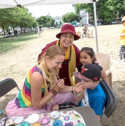 圖為蓮慈上師在畫臉的攤位與小朋友合影。