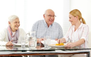 Happy family with senior couple eating lunch at table