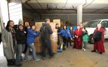 大家將裝箱捐贈的衣物,一起拉進大溫聖誕局倉庫。