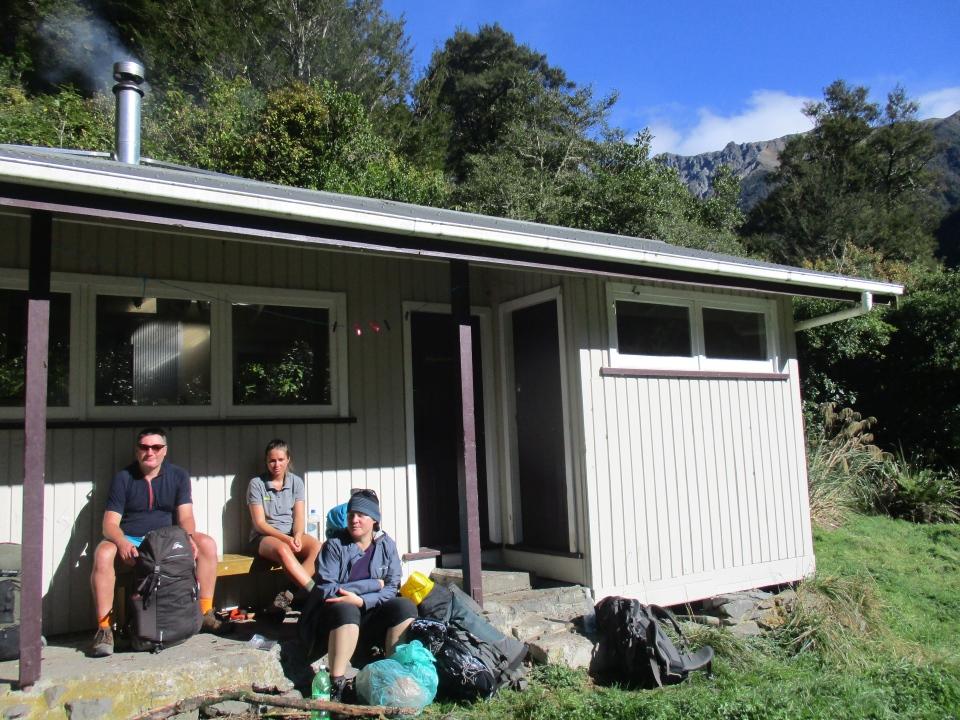 Trampers resting outside Waipawa Forks Hut in the Ruahine Ranges
