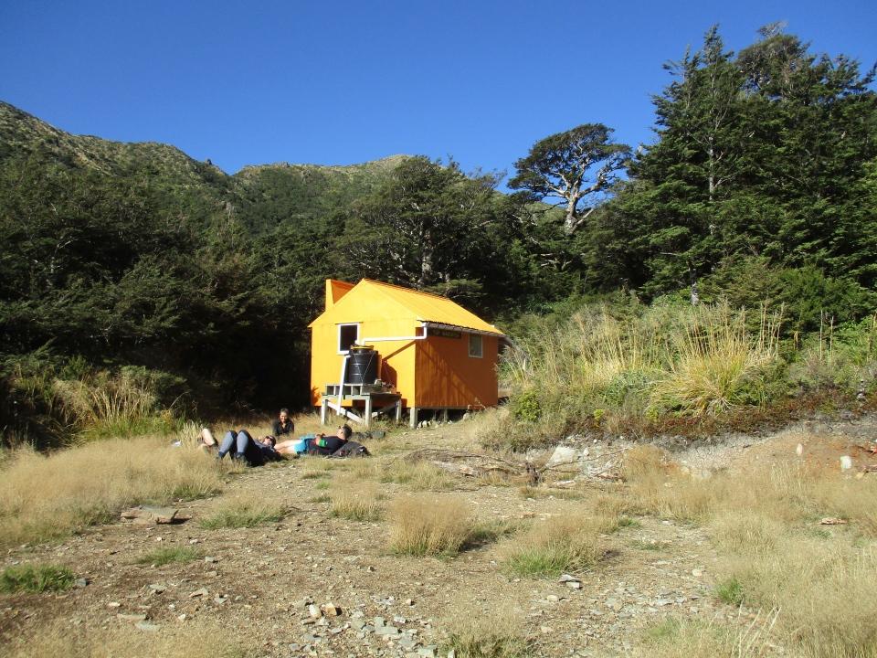Trampers lying in the sun outside Top Maropea Hut