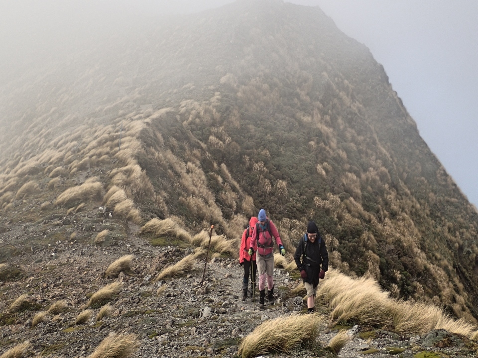 Trampers walking along a ridge in windy conditions