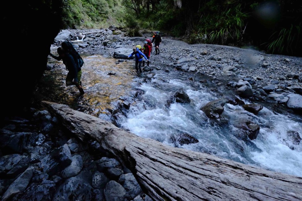 Trampers crossing a river between Black Ridge and Daphne Hut