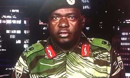 "Zimbabwe Major General Sibusiso Moyo reading a statement at the ZBC broadcast studio in Harare. Zimbabwe's military appeared to be in control of the country on November 15 as generals denied staging a coup but used state television to vow to target ""criminals"" close to President Robert Mugabe"